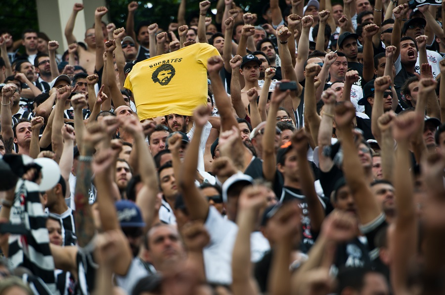 Supporters of Corinthians cheer their team honouring the late footballer Socrates (on T-shirt), during the Brazilian Championship final date match against Palmeiras, at the Pacaembu stadium on December 04, 2011 in Sao Paulo, Brazil. Socrates -former captain of the national team and player of Corinthians- died earlier today at the age of 57 from an intestinal infection. AFP PHOTO / Yasuyoshi CHIBA (Photo credit should read YASUYOSHI CHIBA/AFP via Getty Images)
